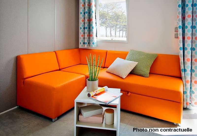 Coin salon avec TV dans mobil home premium au camping du lac à Curbans