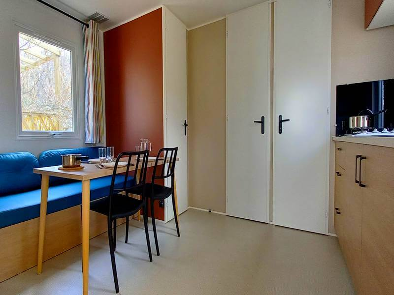 Stacaravan Résidence Ecrins de woonkamer met zithoek en ingerichte keuken op camping Lac in Curbans